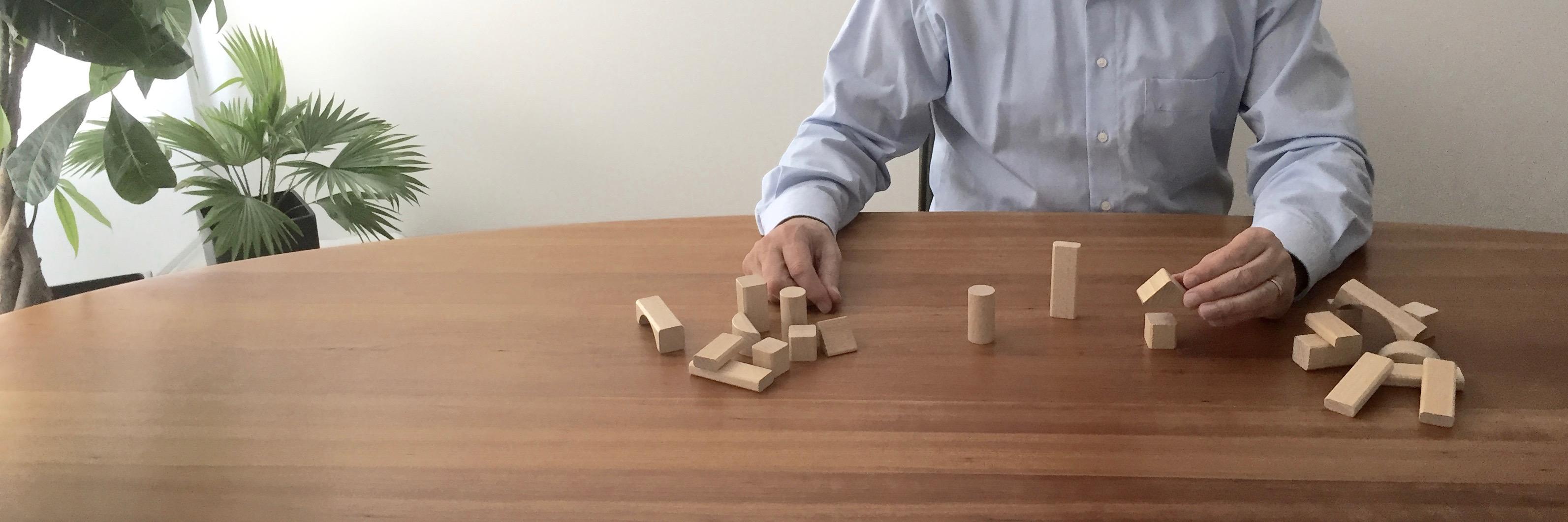 Matthias Zetzl, Inhaber der FinanzKanzlei Bayern, wählt aus einer Menge gezielt Bausteine aus - symbolisch fürs Zusammenstellen einer maßgeschneiderten Versicherungslösung.