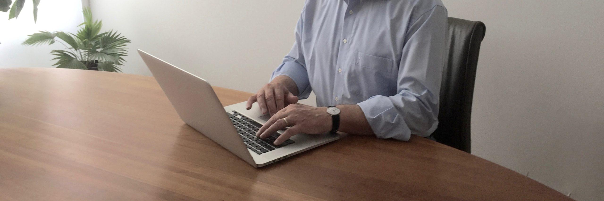 Kunde am Schreibtisch vorm Computer - als Symbol für: Termin online buchen