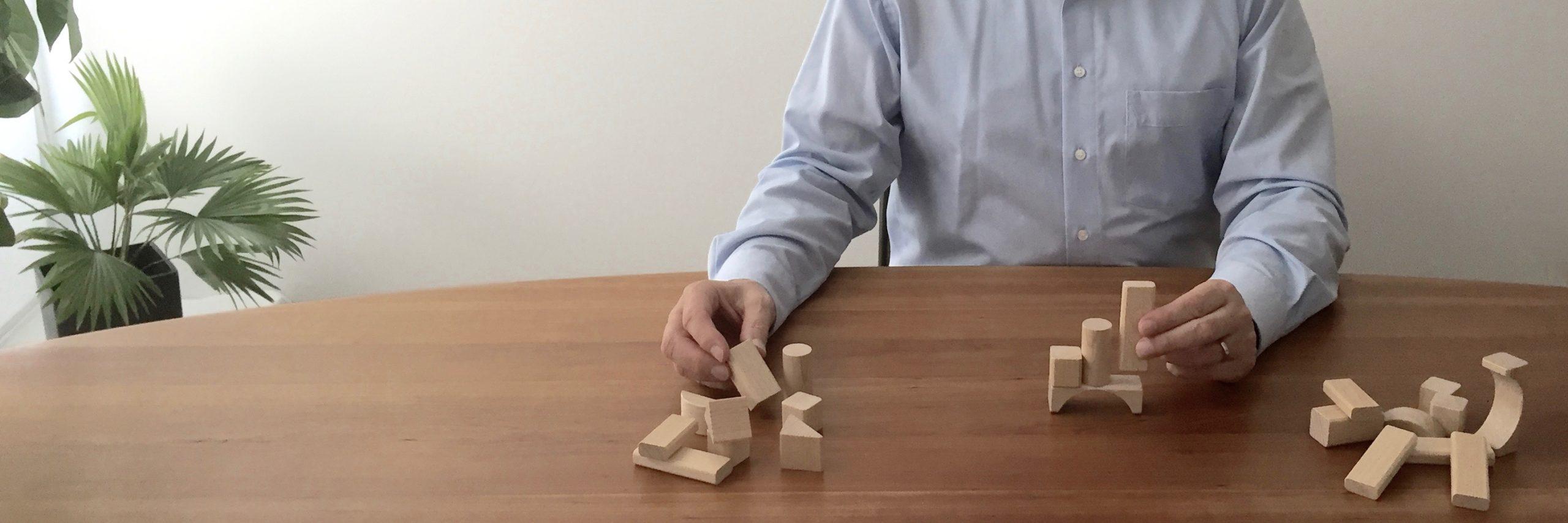 Matthias Zetzl, Inhaber der FinanzKanzlei Bayern, arrangiert am Tisch geschickt Bausteine - symbolisch für: Vermögensmanagement professionell einfädeln